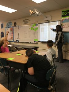 Bank associate teaching students about finances