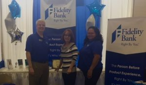 Fidelity Bank employees in front of signs