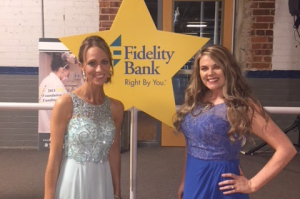 Two employees in front of a Fidelity Bank star sign