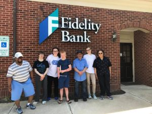Kids and teachers in front of a Fidelity Bank logo