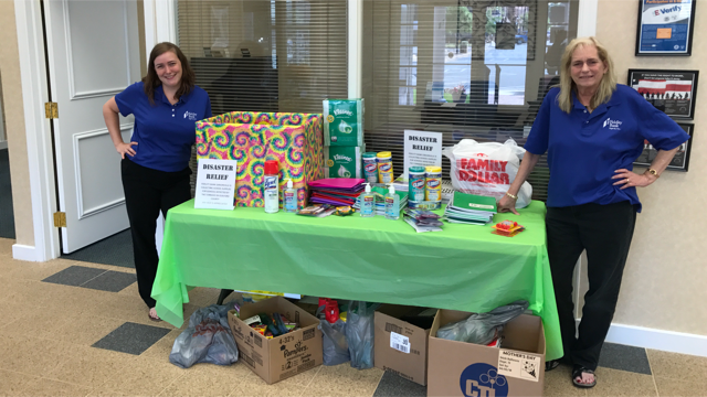 Employees next to a filled table of donations