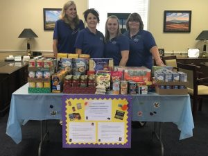 Fidelity Bank employees posing for a photo around donated food