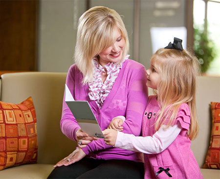 A mother showing her daughter a brochure about Fidelity Bank