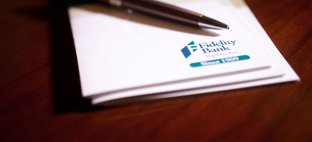 Photo of a Fidelity Bank Notebook and Pen on a table