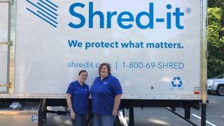 Two Ladies Standing in front of a truck