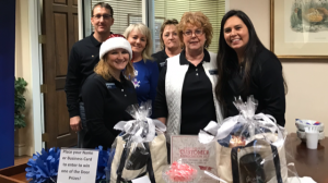 Group of employees posing for a photo around gifts on a table