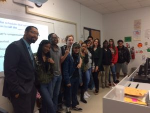 Students lined up in a class posing for a photo with a fidelity bank associate