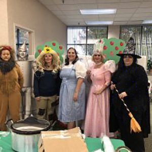 The team dressed up as the Wizard of Oz cast, a lion, the good & bad witches, the scarecrow, and Dorothy.