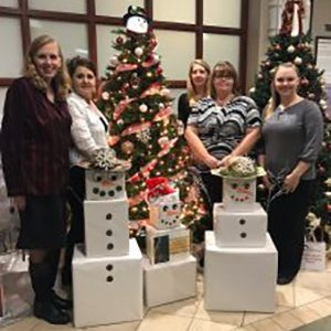 Christmas photo of team posed with boxy snowmen.