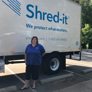 A woman smiles beside a truck reading Shred-it