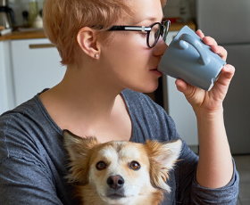 Woman drinking coffee with dog in lap
