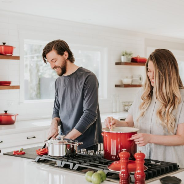 A couple cooking together in their kitchen, laughing