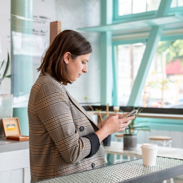 A woman at a cafe checking her phone