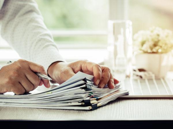 Hands carding through stacks of business paperwork
