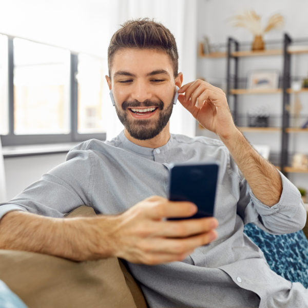 A man smiling joyously as he looks at his phone