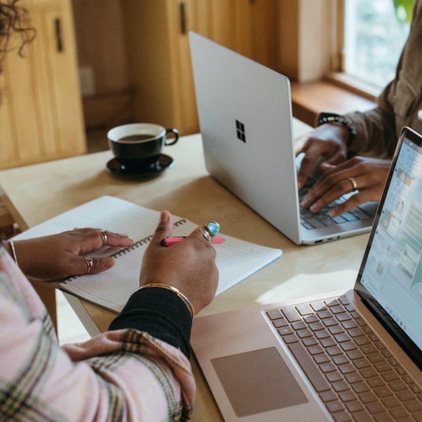 Two women work on laptops