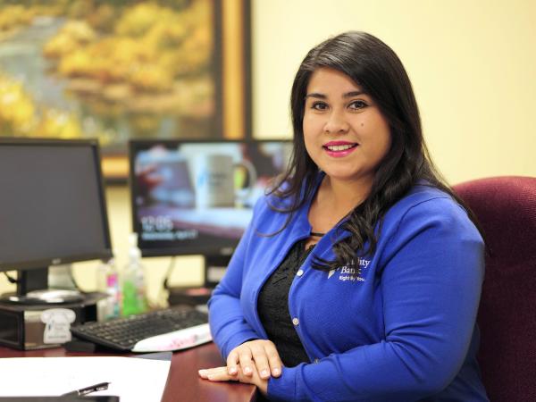 A Fidelity Bank employee behind a desk