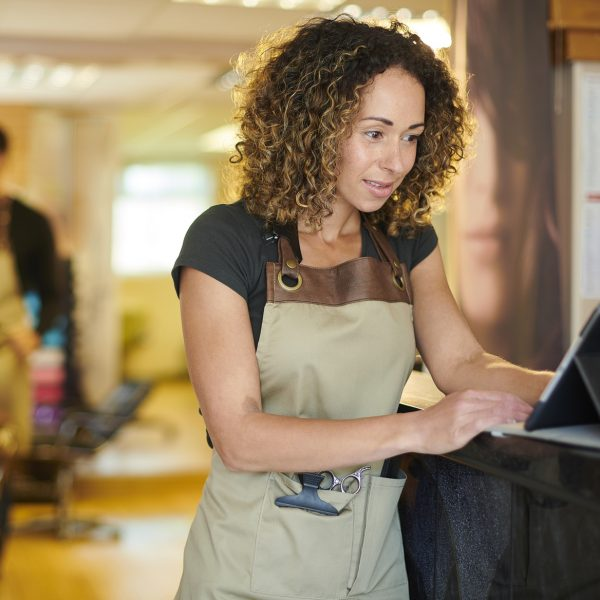 hair salon owner using digital book keeping system