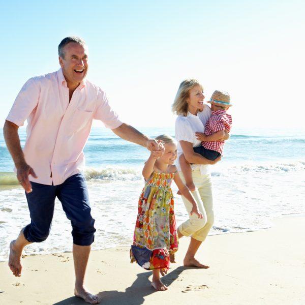 Grandparents and grandchildren enjoying the beach