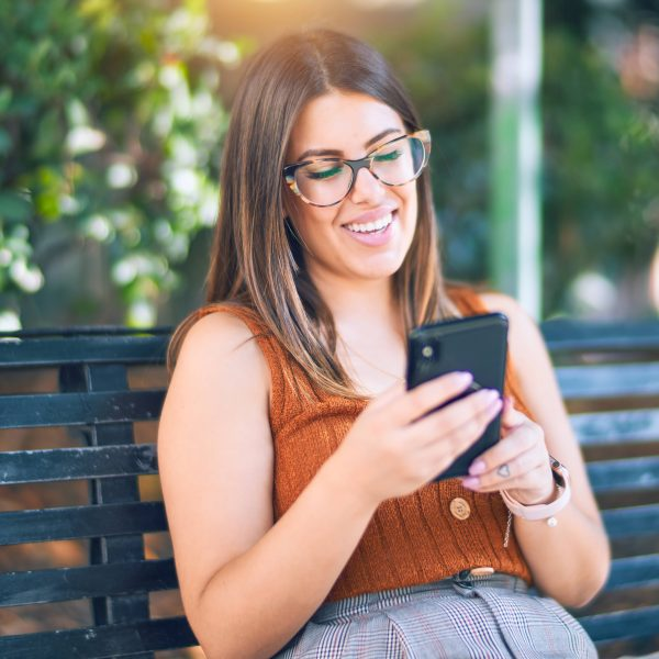 a young woman looking at her phone on a park bench